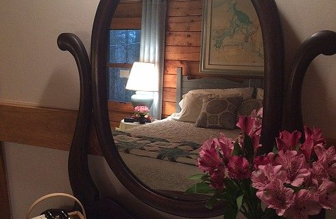 Large oval mirror flowers beside reflecting a king size bed with large painting overhead and side table with lamp near a window