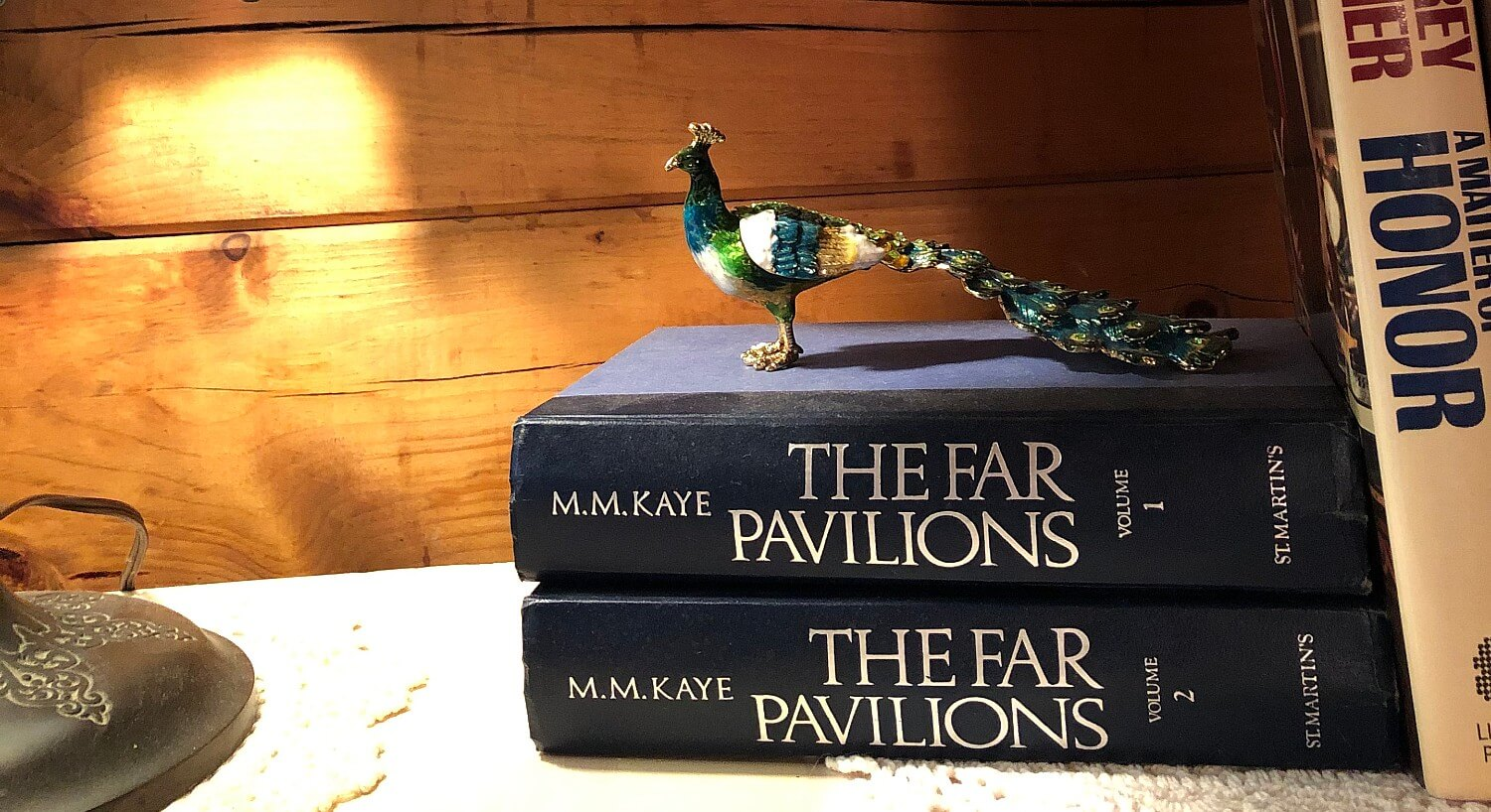 Decorative peacock sitting on two blue hardcover books with white text on a shelf next to a metal lamp base