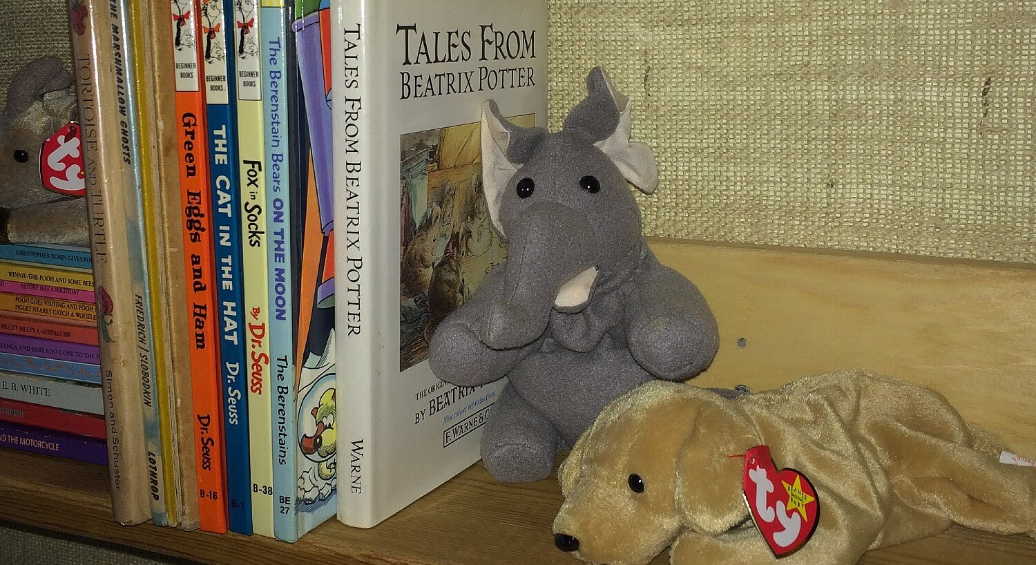 Bookshelf holding several children's books and two stuffed toys; a dog and an elephant