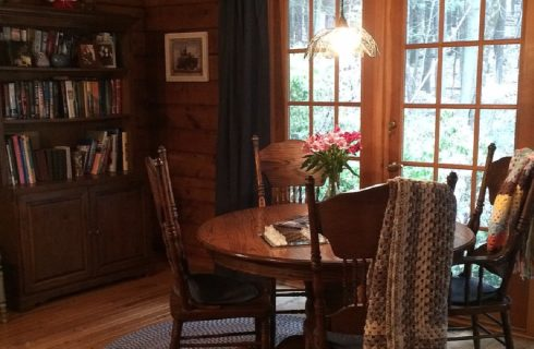 Wood dining table with four chairs under small hanging light next to French doors and tall bookshelf filled with books