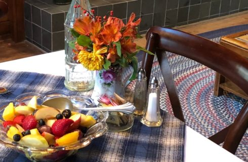 White table with blue plaid cloth holding dish of fruit salad, vase of fresh flowers, salt and pepper and dish of sugar packets