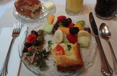 Round glass plate with slice of breakfast quiche and fruit salad with orange juice, coffee and slice of coffee cake