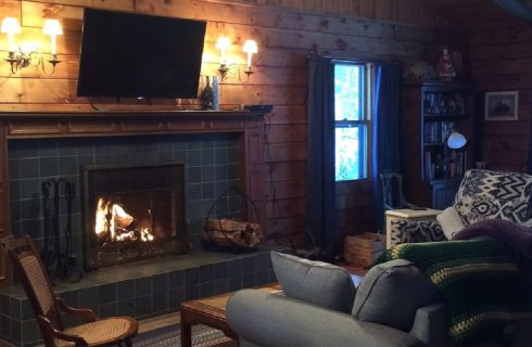 Couch and two chairs in front of a fireplace with TV hung overhead in a cozy wood paneled room with two windows
