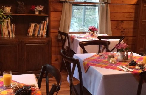 Three tables with white cloths and colorful plaid overlay, in a room with wood paneled walls and tall bookshelf