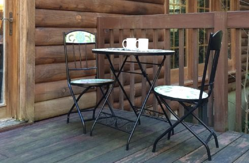 Small bistro table with two white cups, two chairs on an outdoor patio with wooden railing
