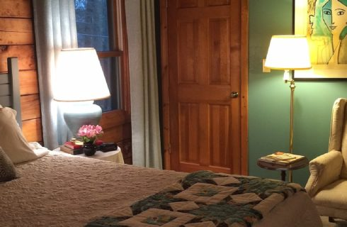 King bed with white quilt, side table with lamp, books and flowers and reading chair in a room with green walls and one window and door