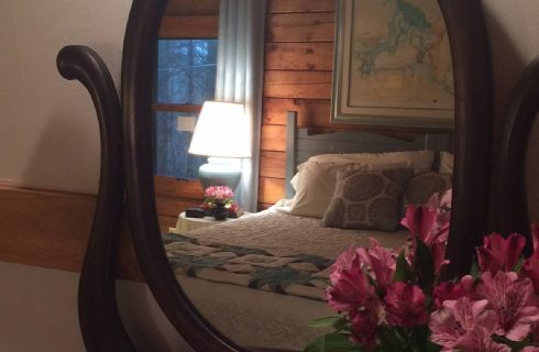 Oval antique mirror reflecting a king bed with blue headboard, white quilt and blue accent pillows wth side table and lamp