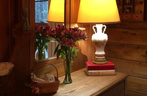 Wood dresser with white lamp on two stacked books, vase of pink flowers and basket of gift items with mirror behind
