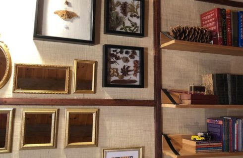 Gallery wall featuring gold framed mirrors, framed leaves and three wooden shelves with books