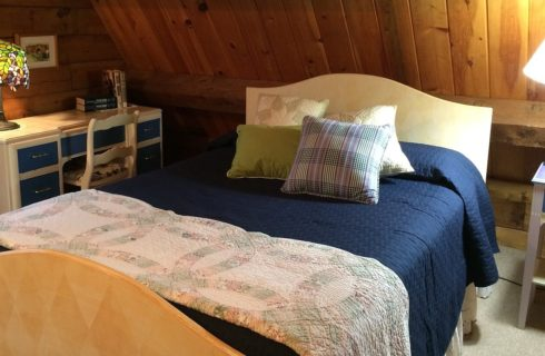 Double sized bed blue and white quilt and accent pillows next to writing desk with multi-colored Tiffany lamp