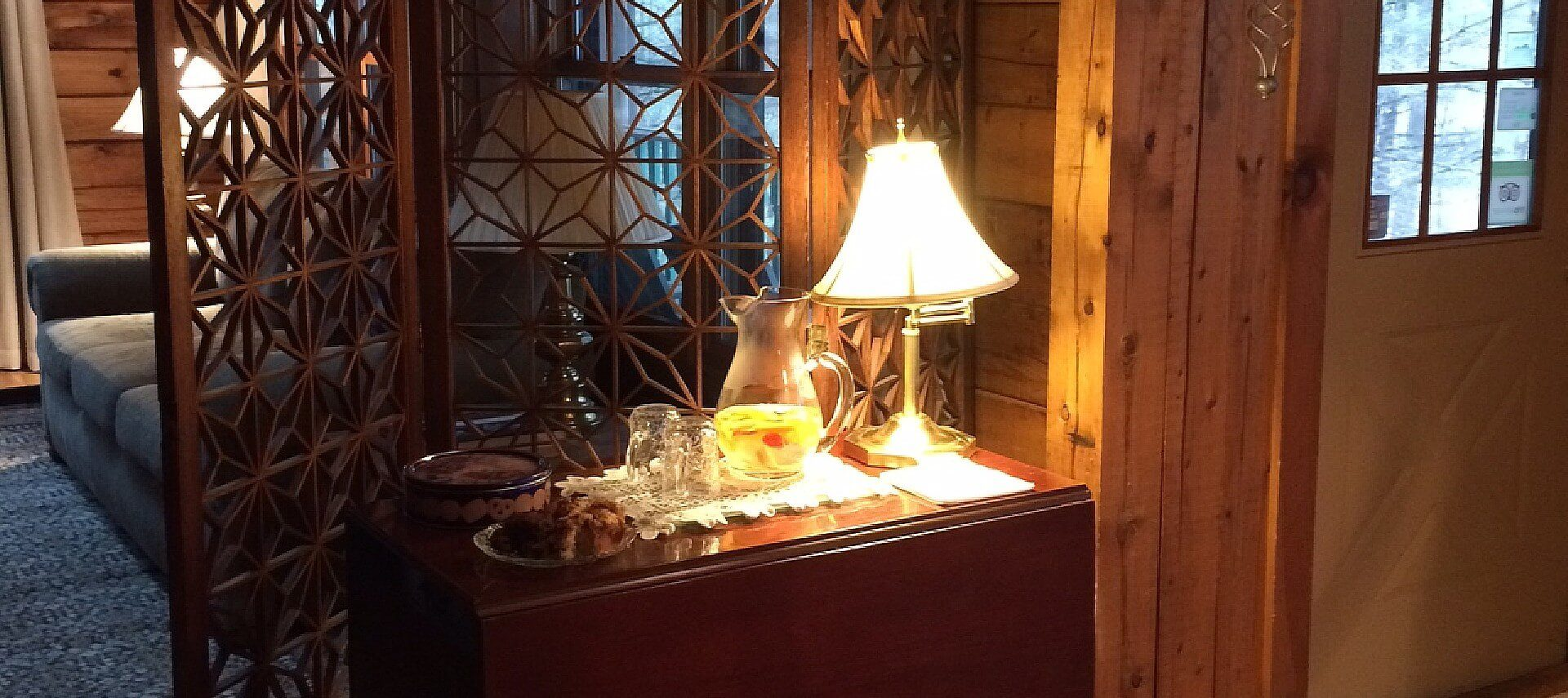 Wood table by a front door holding plate of cookies, pitcher of lemonade, glasses and lamp in front of a tall decorative screen