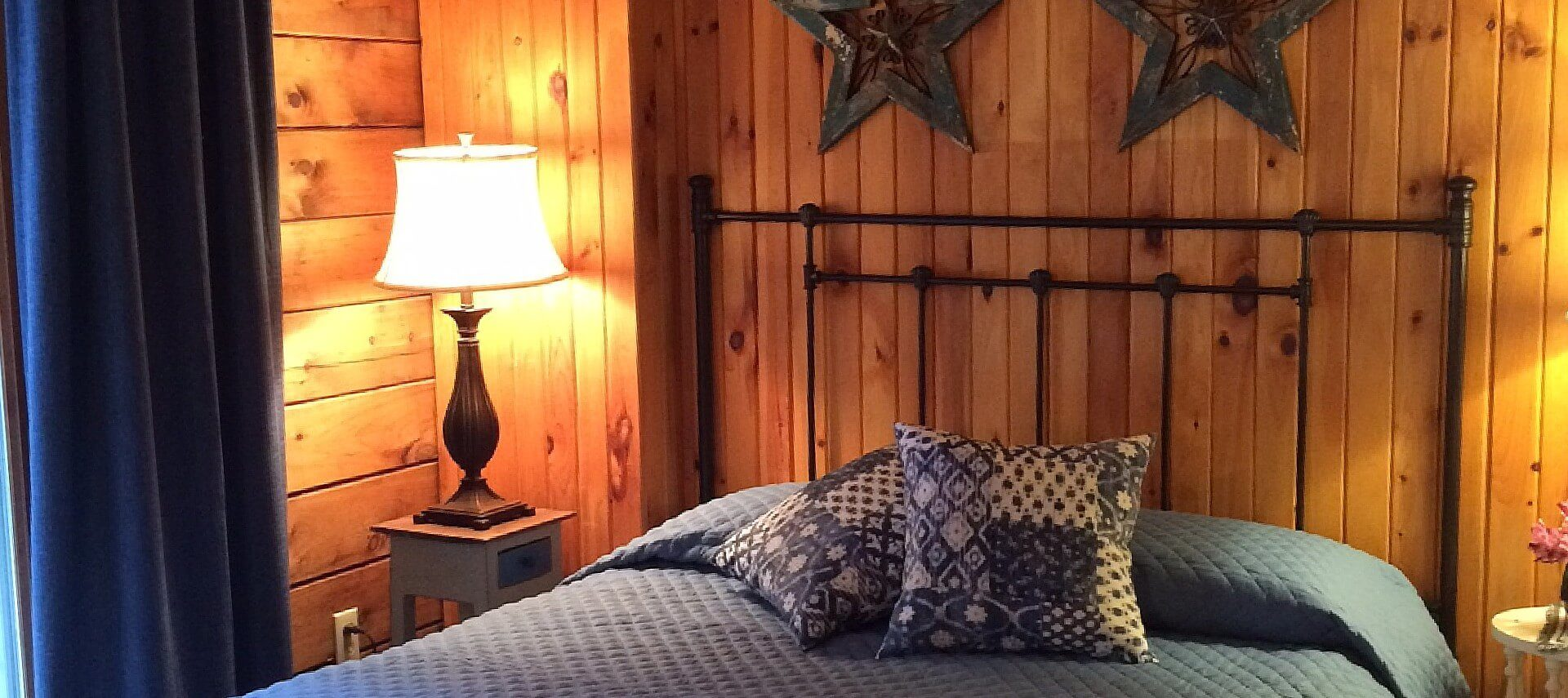Queen bed with black wrought iron headboard and blue quilt, two side tables with lamps in a room with wood paneled walls