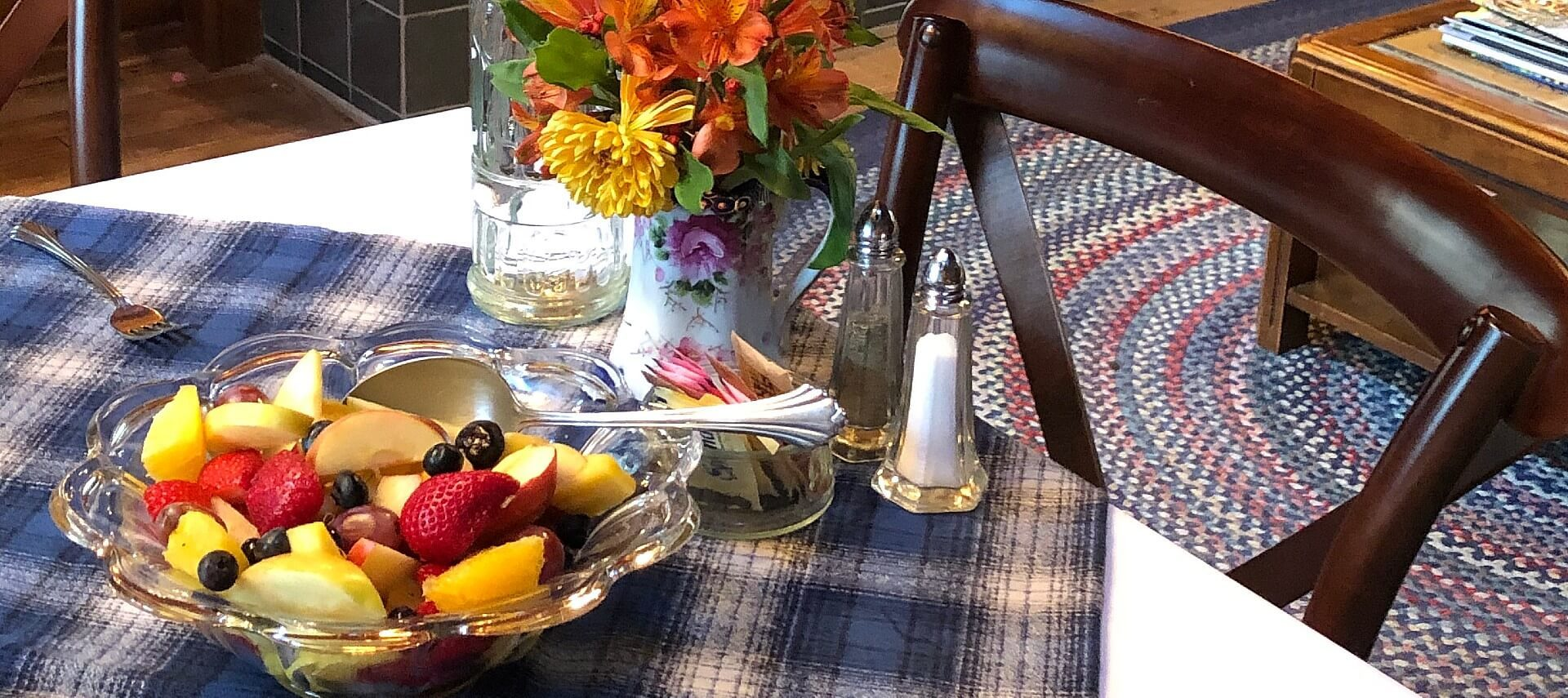Table with blue plaid cloth holding glass bowl of fruit, vase with flowers, salt and pepper and dish of sugar packets
