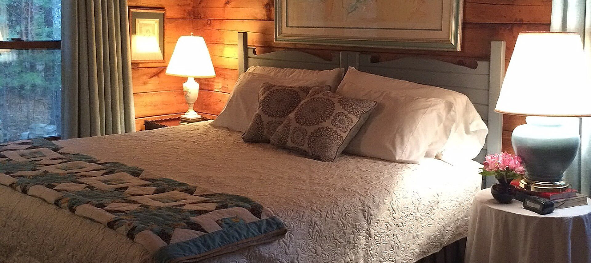 King bed with beautiful white quilt and coverlet, two side tables with lamps next to a large window with curtains