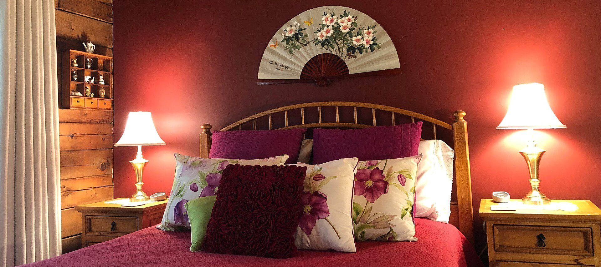 Queen bed with wood headboard and red bedding, two side tables with lamps against a red wall