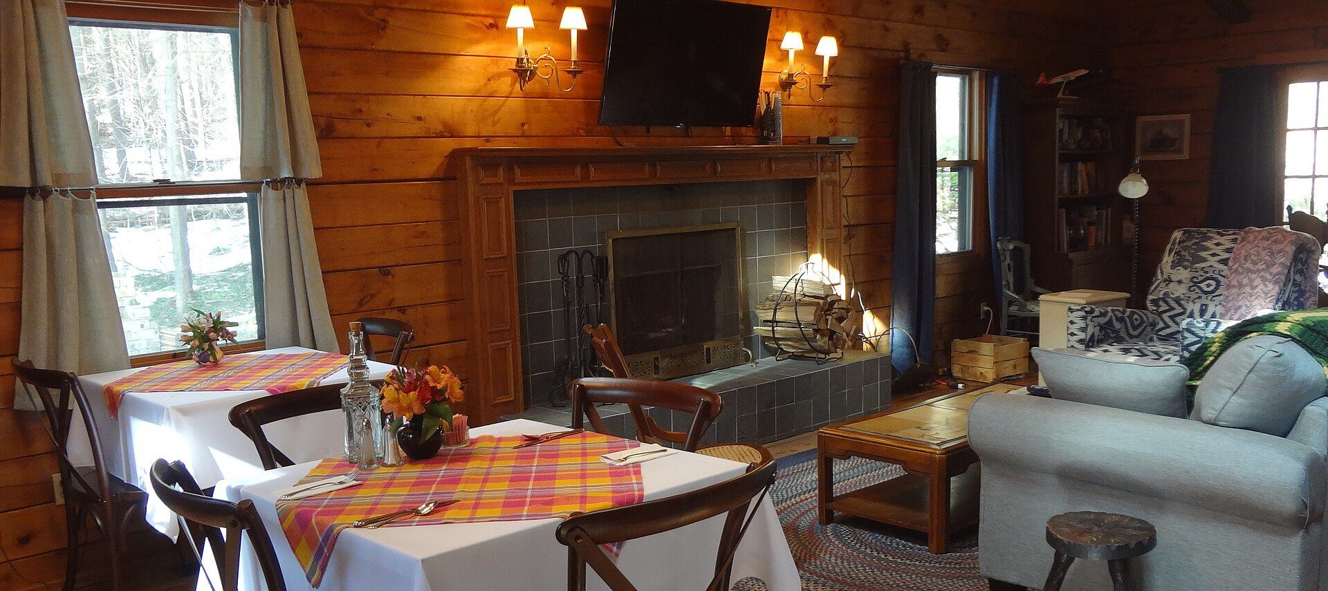 Spacious room with wood paneled walls, couch and chair in front of a fireplace with TV overhead and two dining tables