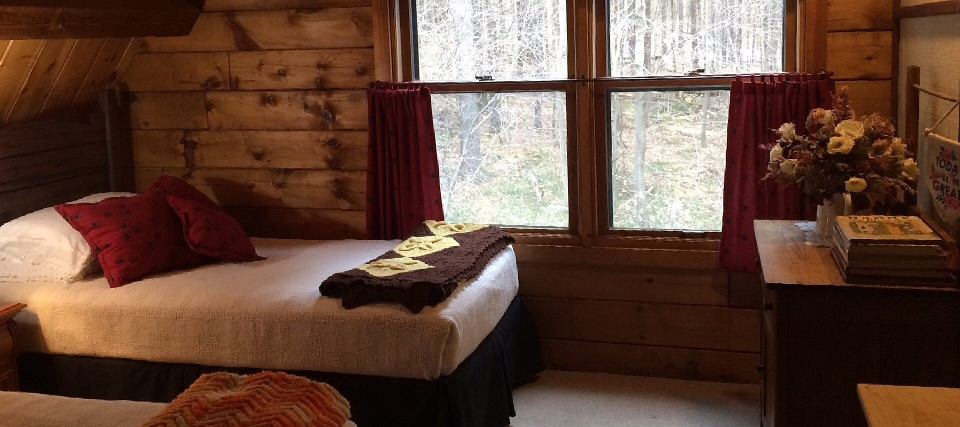 Twin bed with white quilt and red pillows underneath a large window with red curtains and views into a wooded area