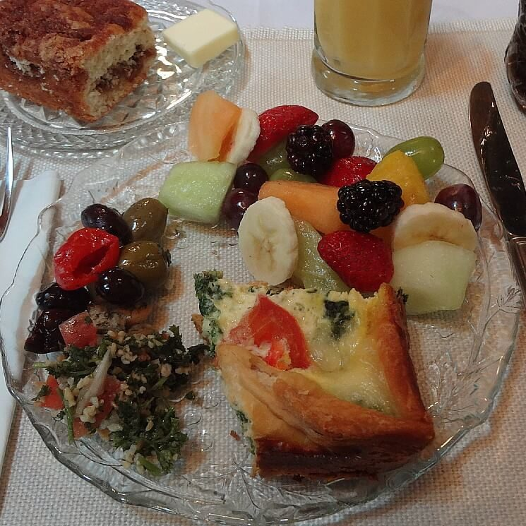 Round glass dish with olives, breakfast quiche, fruit salad next to glass of orange juice and plate of coffee cake