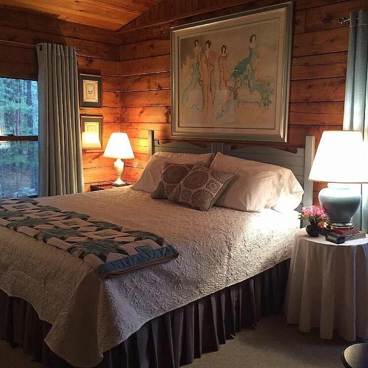 King bed with beautiful white and blue quilts, side tables with lamps and large painting above in wood paneled room