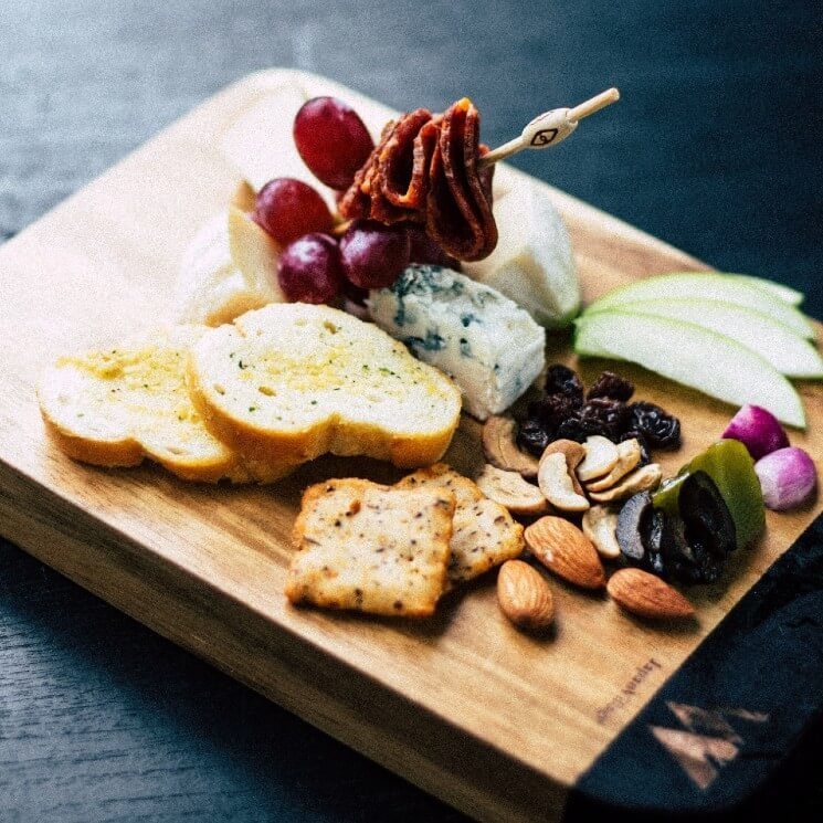 Charcuterie board with bread, crackers, nuts, apples, cheeses and skewer of grapes and meat