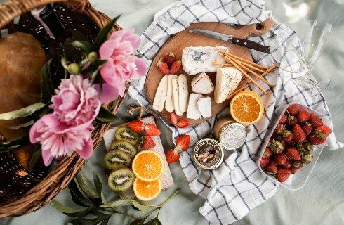 Board of cheese and fruit on a white and black checkered napkin net to a wooden basket with pink flowers
