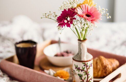 Wooden tray on a bed holding cup of coffee, croissant, bowl of fruit and vase with daisies